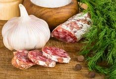 Отрезанное salame на разделочной доске, с укропом, перец, соль стоковые фото