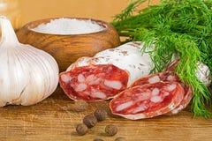Отрезанное salame на разделочной доске, с укропом, перец, соль стоковое фото