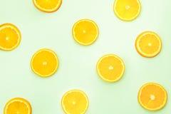 Отрезанные апельсины на зеленой предпосылке, взгляд сверху Стоковое Изображение