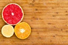 Отрезанные грейпфрут, апельсин и лимон на деревянной доске Стоковое Изображение RF
