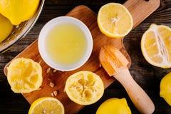 Отрезанные и сжиманные половины лимона на деревянной предпосылке Стоковая Фотография RF