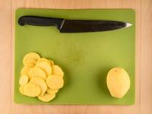 Отрезанные картошки и нож на доске пластмассы пользы Стоковая Фотография