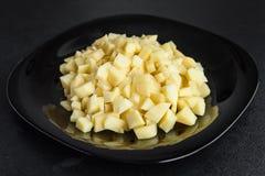 Отрезанные картошки на черной плите Стоковые Изображения RF