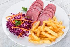 Отрезанные копченые филе телятины, фраи француза и салат красной капусты стоковые изображения