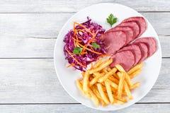 Отрезанные копченые филе телятины, фраи француза и салат красной капусты стоковая фотография