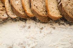 Отрезанные куски хлеба на деревянном столе с мукой Стоковые Изображения RF