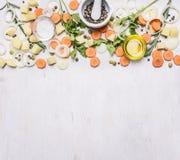 Отрезанные моркови, травы, луки, масло, приправа, отрезали картошки, границу перца точильщика миномета, текст места на деревянное Стоковое Фото