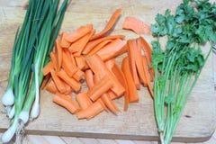 Отрезанные моркови ‹â€ ‹â€, лук и листья кориандра на коричневом butche Стоковые Изображения RF