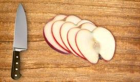 Отрезанные плодоовощ и нож яблока на разделочной доске Стоковая Фотография RF