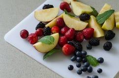 Отрезанные свежие яблоки, клубники, голубики, ежевики и листья мяты вокруг Стоковые Фото