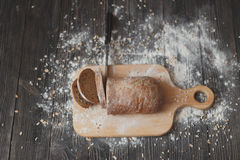 Отрезанные хлеб и нож на деревянном крупном плане разделочной доски Стоковые Изображения