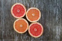 Отрезанные цитрусовые фрукты апельсин, грейпфрут над деревянной предпосылкой Стоковые Фотографии RF