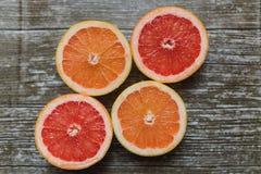 Отрезанные цитрусовые фрукты апельсин, грейпфрут над деревянной предпосылкой Стоковые Фото