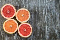 Отрезанные цитрусовые фрукты апельсин, грейпфрут над деревянной предпосылкой Стоковые Изображения