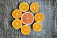 Отрезанные цитрусовые фрукты апельсин, грейпфрут над деревянной предпосылкой Стоковое Фото