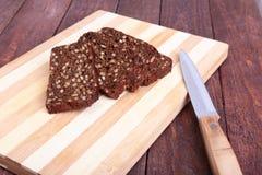 Отрезанные черный хлеб и нож на старой деревянной планке Стоковое Изображение RF