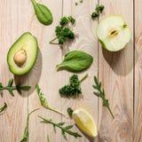 Отрезанный авокадо и свежие сырцовые зеленые цвета на деревянной предпосылке Стоковая Фотография