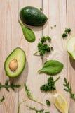 Отрезанный авокадо и свежие сырцовые зеленые цвета на деревянной предпосылке Стоковое Изображение RF