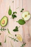 Отрезанный авокадо и свежие сырцовые зеленые цвета на деревянной предпосылке Стоковые Изображения