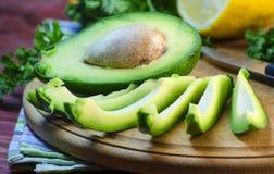 Отрезанный авокадо на разделочной доске Стоковая Фотография