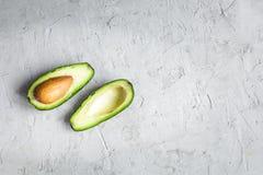 Отрезанный авокадо ‹â€ ‹â€ на доске и конкретной предпосылке Стоковые Фотографии RF