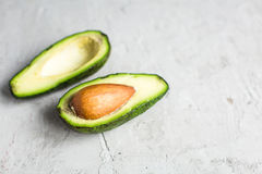Отрезанный авокадо ‹â€ ‹â€ на доске и конкретной предпосылке Стоковое Фото