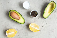 Отрезанный авокадо ‹â€ ‹â€ на доске и конкретной предпосылке Стоковое Изображение RF