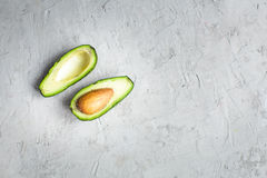 Отрезанный авокадо ‹â€ ‹â€ на доске и конкретной предпосылке Стоковые Фото