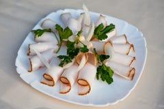 Отрезанный аппетитный шпик с луком и петрушкой на плите стоковые изображения