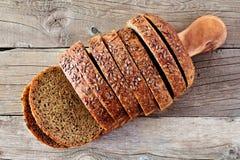 Отрезанный весь хлеб зерна с льном, над взглядом на древесине Стоковое Изображение RF