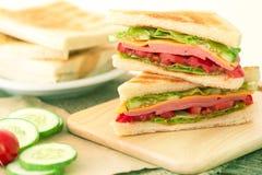 Отрезанный зажаренный хлеб сандвичей с беконом, ветчиной и сыром с Стоковые Изображения