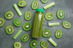 Отрезанный зеленый зрелый киви, черенок сельдерея и бутылка Стоковые Изображения