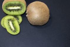 Отрезанный зеленый киви на черной предпосылке Стоковое Изображение RF