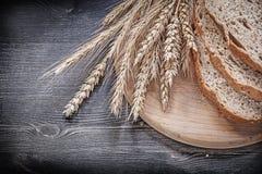 Отрезанный коричневый хлеб на деревянном высекая horizo ушей рож пшеницы доски Стоковые Изображения RF