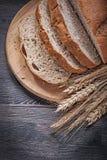 Отрезанный коричневый хлеб на деревянных высекая ушах рож пшеницы доски золотых Стоковые Изображения RF
