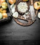 Отрезанный лук на разделочной доске с старым топориком Стоковая Фотография RF