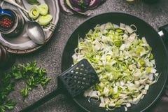 Отрезанный лук-порей в черной сковороде на деревенской предпосылке кухонного стола, взгляд сверху Здоровый вегетарианец варя и ес Стоковая Фотография