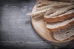 Отрезанный покрытый коркой хлеб на деревянных высекая ушах рож пшеницы доски зрелых Стоковые Фото