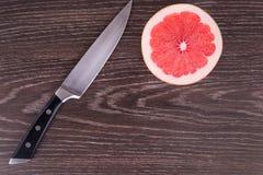 Отрезанный плодоовощ и нож на деревянной предпосылке Стоковое Фото