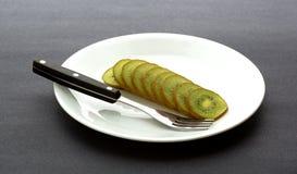 Отрезанный плодоовощ кивиа на плите с вилкой Стоковое Изображение RF