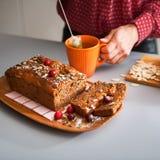 Отрезанный самодельный хлебец хлеба тыквы, рук женщины и чая стоковые фото