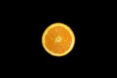 Отрезанный свежий апельсин на глубоком черном backround Стоковые Изображения RF