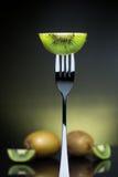 Отрезанный свежий и сочный зеленый киви на вилке с всем кивиом внутри Стоковые Изображения
