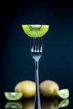 Отрезанный свежий и сочный зеленый киви на вилке с всем кивиом внутри Стоковые Изображения RF