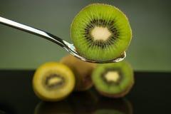 Отрезанный свежий и сочный зеленый плодоовощ кивиа на ложке с всем кивиом Стоковая Фотография RF