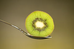 Отрезанный свежий и сочный зеленый плодоовощ кивиа на ложке с желтым lig Стоковые Фотографии RF