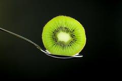 Отрезанный свежий и сочный зеленый плодоовощ кивиа на ложке с задней частью черноты Стоковые Изображения