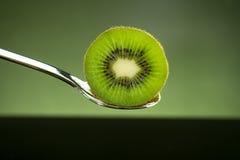 Отрезанный свежий и сочный зеленый плодоовощ кивиа на ложке с зеленым ligh Стоковые Фотографии RF