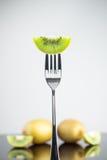 Отрезанный свежий и сочный зеленый киви на вилке с всем кивиом внутри Стоковая Фотография