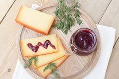 Отрезанный соус сыра и вишни на деревянной доске с укропом и розмариновым маслом Стоковое фото RF